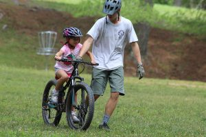 young girl learning to ride mountain bike